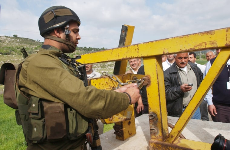 An Israeli army soldier opens the gate of Anabta in the outskirts of the West Bank town of Tulkarem, Tuesday.
