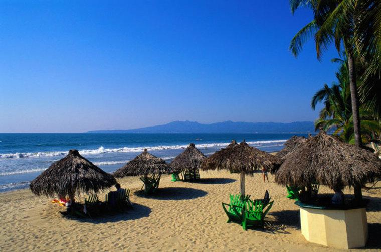 Grass umbrellas on beach, Puerto Vallarta, Mexico