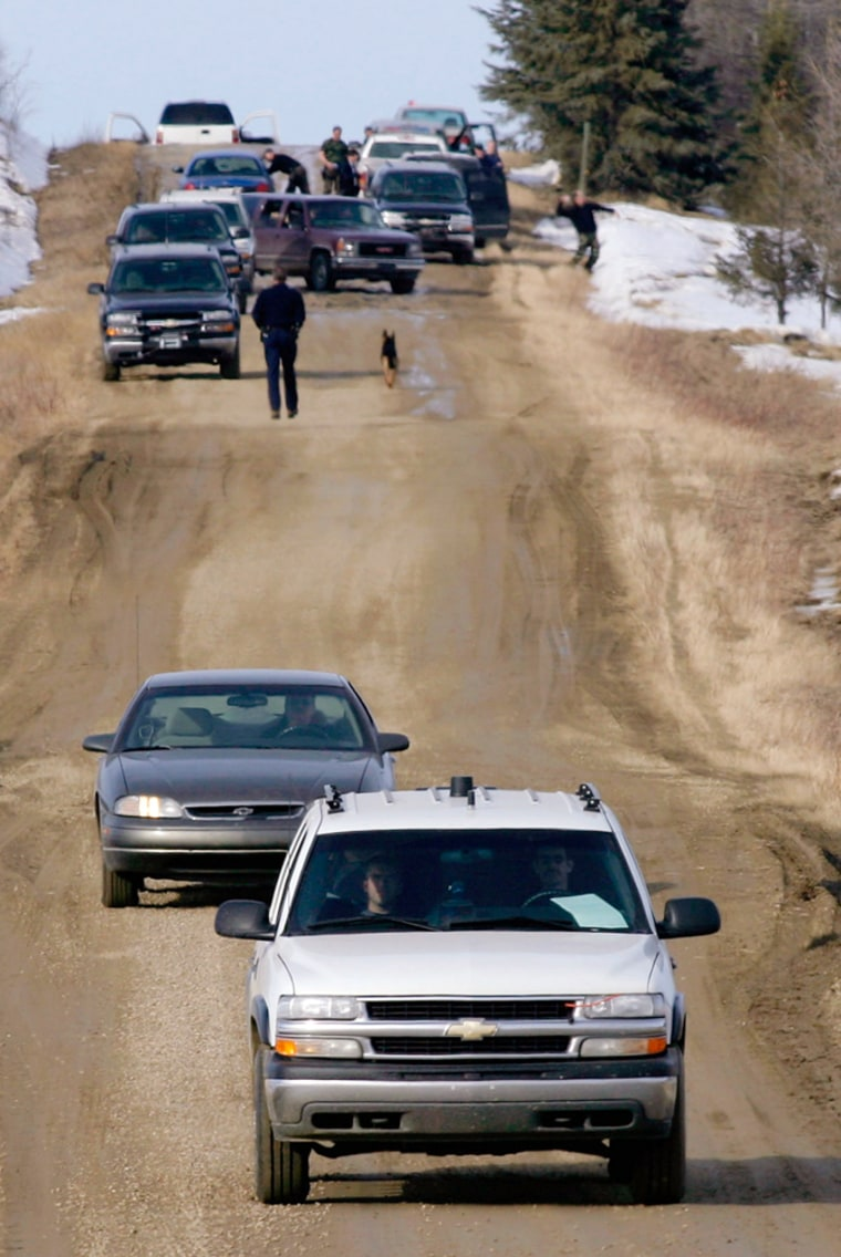 Police leave the property where four Alberta RCMP officers were shot dead during an investigation into a marijuana farm near the village of Rochfort Bridge, in northwestern Alberta, Canada, on Thursday.