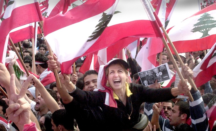Protestors wave Lebanese flags during a demonstration against Syria in Beirut on Monday.