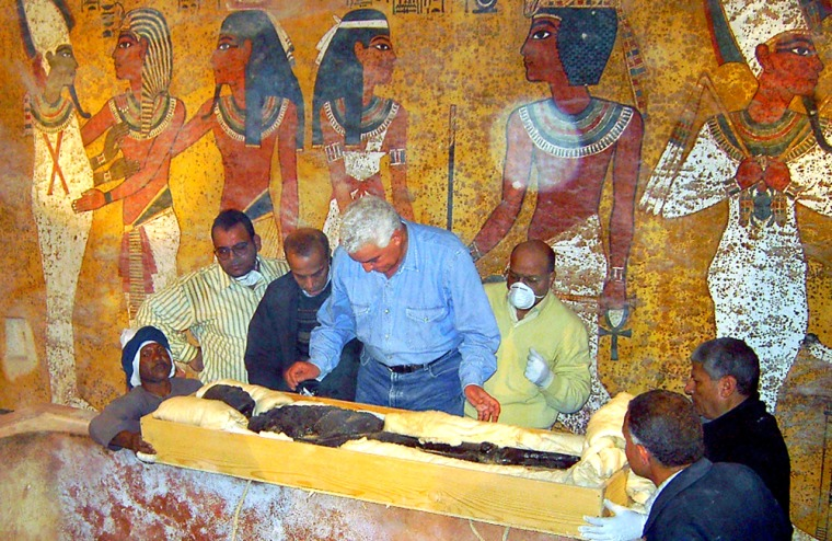 Zahi Hawass, the head of the Egyptian Supreme Council for Antiquities, center, checks the 3,300-year-old mummy of the ancient King Tutankhamun at his tomb in Luxor, Egypt.