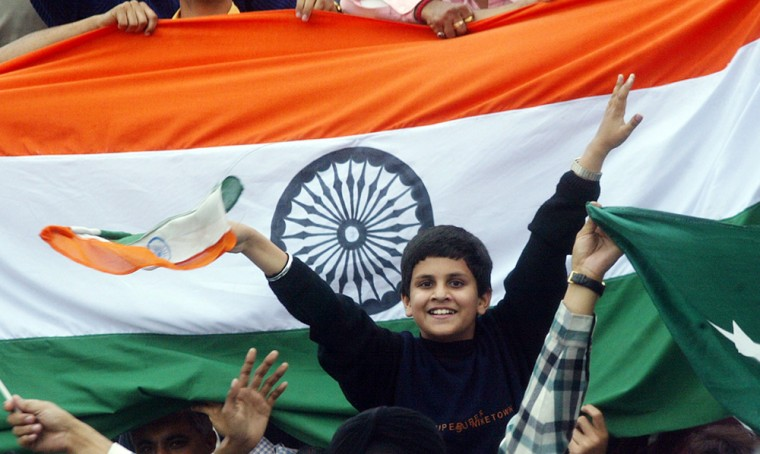 An Indian boy cheers for his cricket team during a test match in Mohali