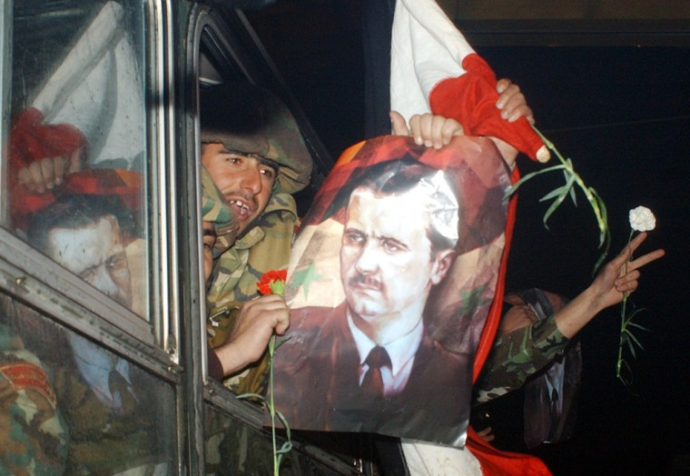Syrian troops withdrawing from Lebanon display Syrian flags along with posters of President Bashar Assad as they cross the Syrian-Lebanese border early Saturday.