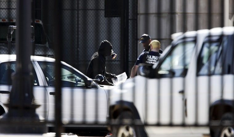 Emergency crews wear breathing devices Monday near the entry to a mail facility at the Pentagon. Hazmat crews responded to the facility after an alert went off for a possible hazardous material.