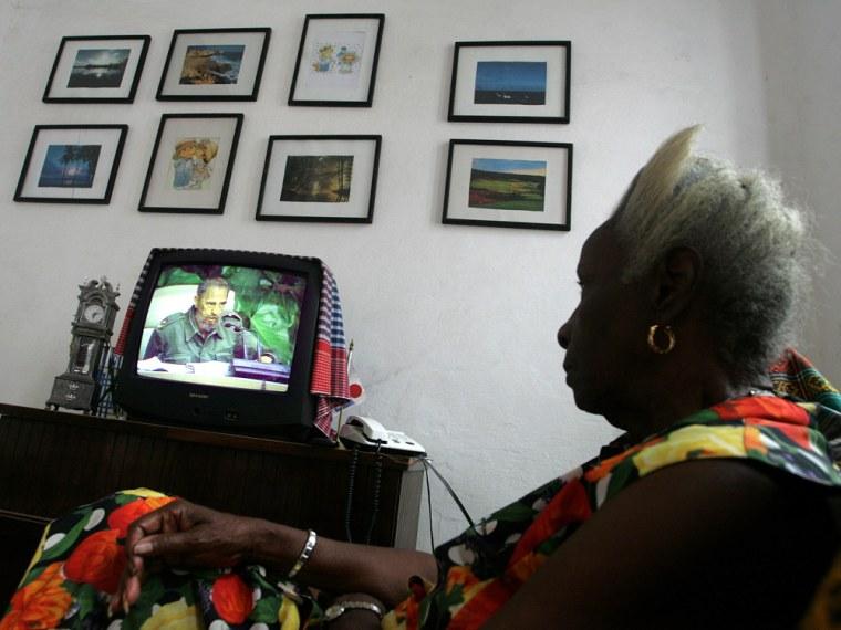 Havana resident watches Cuban President Castro speaking on TV