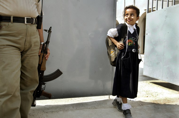An Iraqi girl passes by an armed security guard as she leaves school in Baghdad in October.