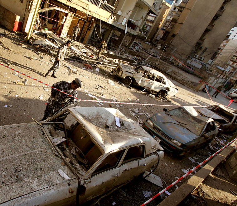 A police officer looks at a damagedvehicle after a car bomb exploded in the New Jdeideh neighborhood, in the northern suburbs of Beirut, Lebanon, on Saturday.