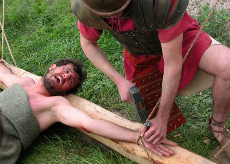 """A volunteer grimaces for the camera during filming for """"The Quest for Truth: The Crucifixion,"""" airing Sunday. The volunteer was tied to a cross to study the biomechanics of crucifixion, but no one was actually hurt. The simulatednailing was just for show."""