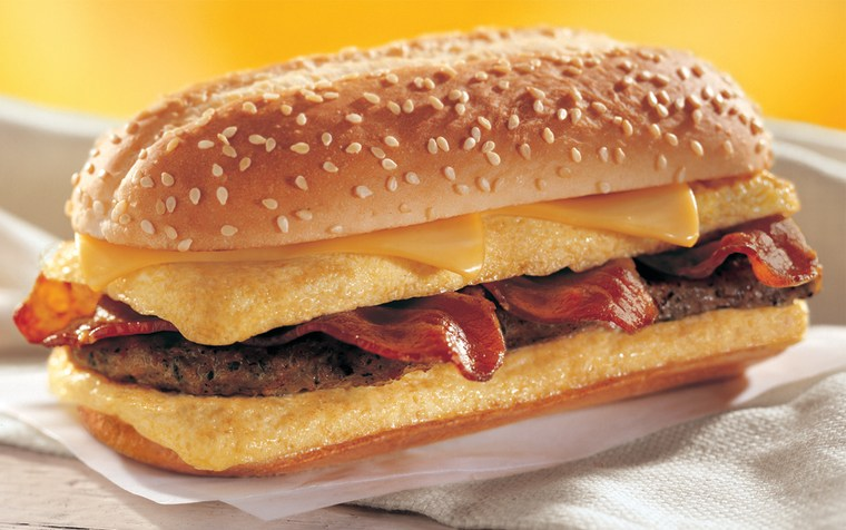 """The """"Enormous Omelet Sandwich"""" contains two slices of melted, American cheese, two fluffy eggs stuffed with three crispy strips of bacon, and asausage patty, piled high on a toasted bun."""