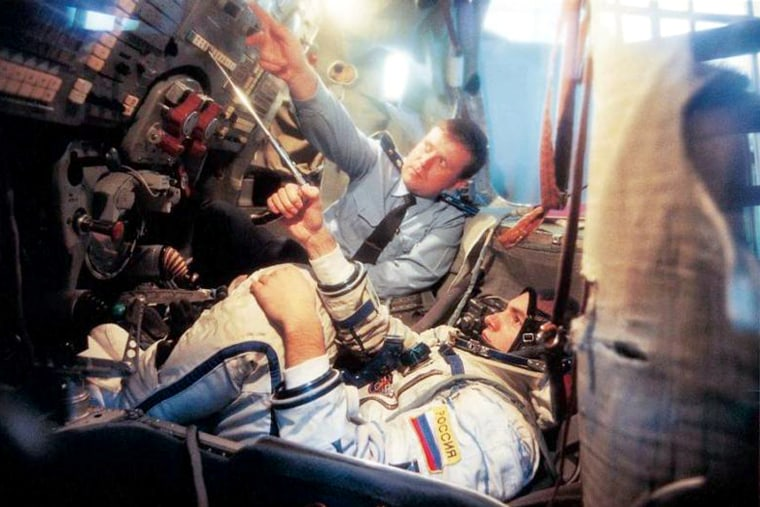 In a 2002 photo, commercial space passenger Mark Shuttleworth undergoes training inside a Soyuz capsule mock-up. This week, trainers briefly suspended such training for NASA astronauts, a gesture sparked by disagreements over the financial arrangements for future Soyuz flights.