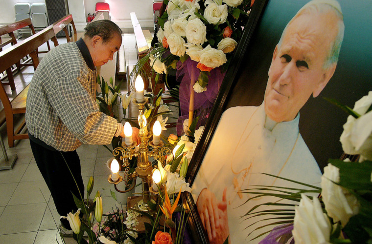 A man prepares a symbolic funeral bier for a service dedicated to the late Pope John Paul II at a government-approved Catholic church in Shanghai on Friday. Chinese are officially permitted to worship only in government-approved churches which do not recognize the authority of the Vatican.