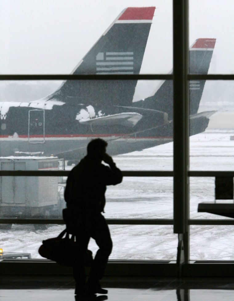 Passenger walks past snow-covered US Airways jets at National Airport in Washington during a winter storm