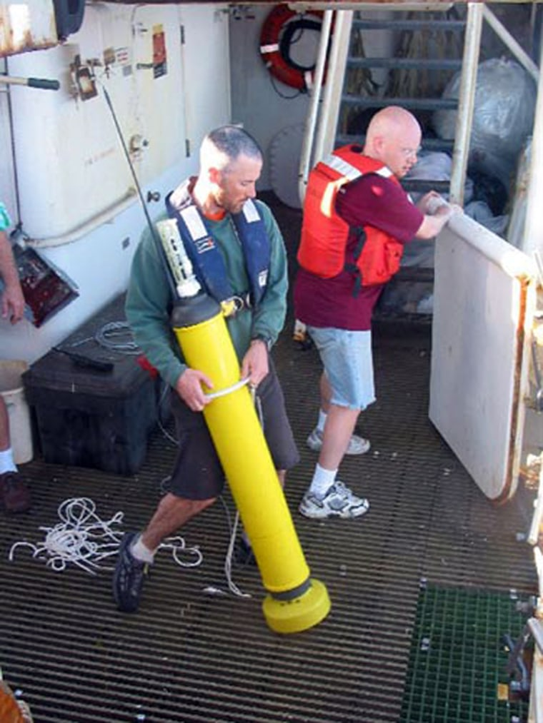 """Researchers with the National Oceanic and Atmospheric Administration prepare to launch a """"profiling float"""" in the tropical Pacific. The float is one of hundreds used around the world to monitor climate change and which were instrumental for a new report on warming and human greenhouse gas emissions."""