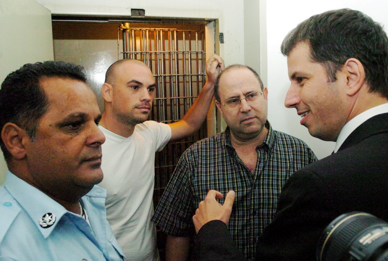 An unidentified lawyer, right, speaks outside a Tel Aviv court with private investigators Zvika Krochmal, second right, and Ofer Fried, second left, who were both arrested as part of a police investigation into the computer espionage scandal.