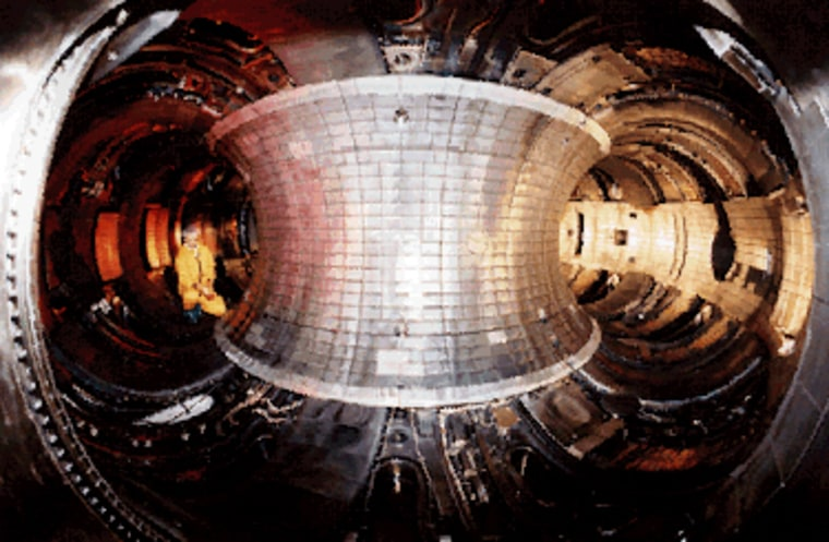 A scientist is seen inside a fusion reactor that had been used by the Energy Department and Princeton University to heat hydrogen atoms so that they become plasma and then energy. The reactor was disassembled in 2003 after 15 years of research use.