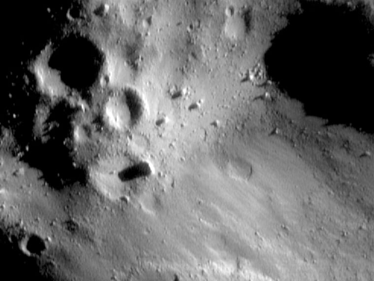 "This image shows pooling of regolith and small boulders in low areas of the asteroid Eros, plus degraded craters, nearly erased ""ghost"" craters and a very few small craters."