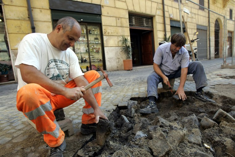 Workers remove cobblestones from a street in Rome,July 22. The ancient stones are costly to lay and maintain.