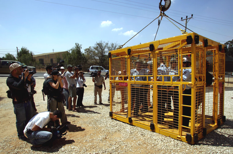 Reporters take pictures Tuesday of Israeli border policemen in a cage to be used during the evacuation of a Jewish settlement, during an exerciseat Zeelim military base, in southern Israel.