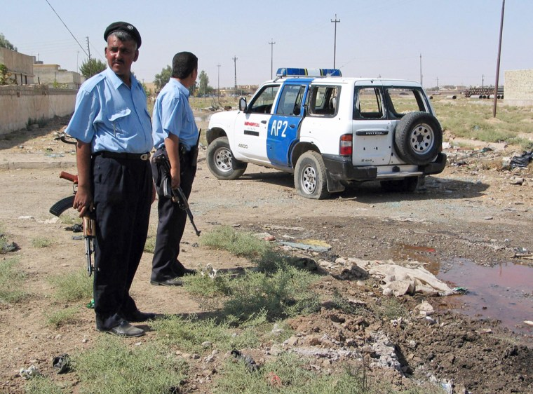 Police officers stand next to a damaged police vehicle after roadside bomb attack in Kirkuk