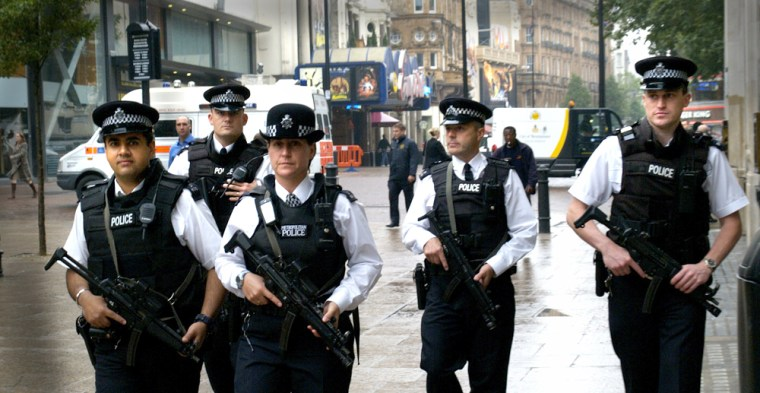 Armed British police patrol London's Leicester Square on Thursday. The search for three suspected London bombers continued, as the interrogation of one suspect began — with caution.
