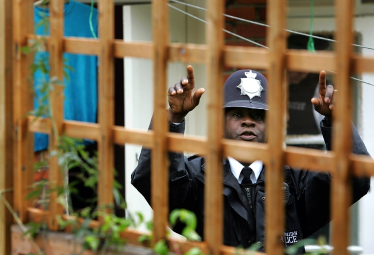 A police officer gestures at the rear of