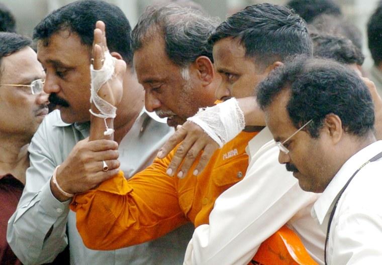 Indian officials escort an injured survi