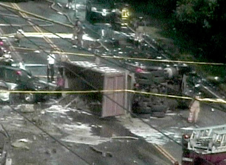 A dump truck lies on its side Friday after a fiery crash shut down Route 44 near Avon, Conn.