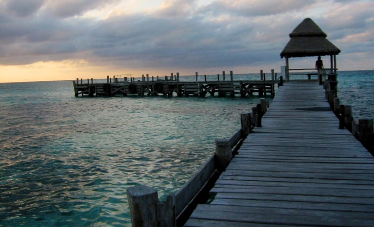 The sun sets near Playa Norte on Isla Mujeres, an island off the Yucatan Coast, Mexico. On the island, it's possible to enjoy a luxurious remoteness and local flavor, at a relatively low cost.