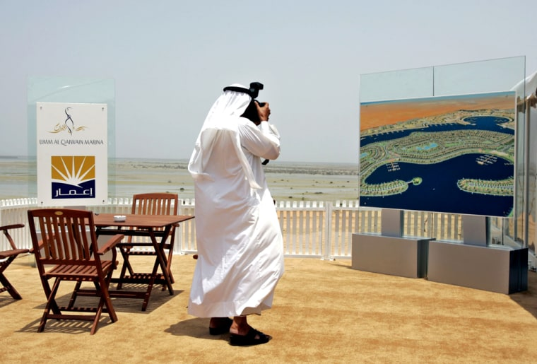 An Emirates photographer takes a picture of a billboard that shows the$3.3 billionUmm Al Quwain Marina developement, to be builton a vast wildlife area on the Gulf waters about 40milesnorth of Dubai, United Arab Emirates.