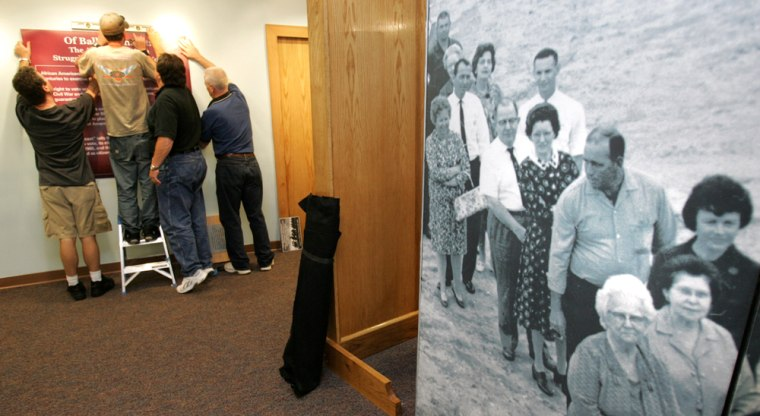 A historical photo of a whites-only voting line is part ofthe exhibit at the Martin Luther King Jr. National Historic Site in Atlanta. At left workers hang posters that are part of the exhibit.