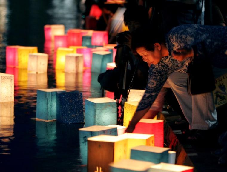 Japanese elderly woman floats paper lantern on Motoyasu river in Hiroshima, Japan