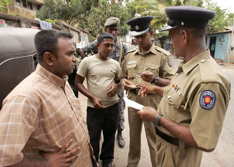 Sri Lankan policemen conduct security check on street in Colombo
