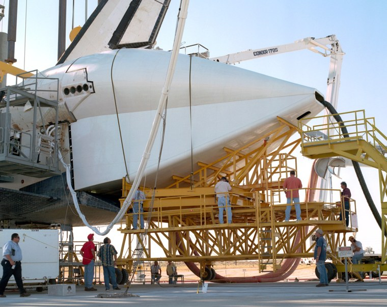 Technicians attach the tail cone to the space shuttle Discovery on Tuesday in preparation for its return to NASA's Kennedy Space Center in Florida.