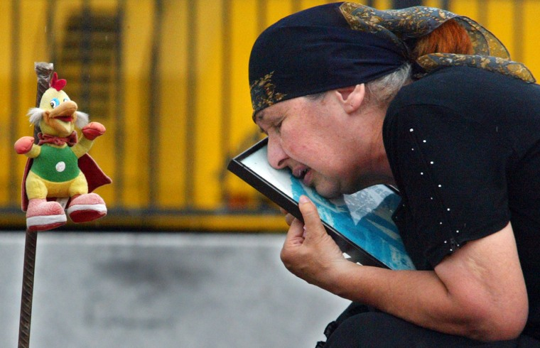 A motherkisses a portrait of her daughter, who waskilled in the Beslan schoolsiege, at the cemetery in Beslan, Russia, earlier this month. To mark the first anniversary of the bloodbath,workersare laying polishing red granite tombstones at the graveyard, where the victims wereburied under simple wooden crosses.