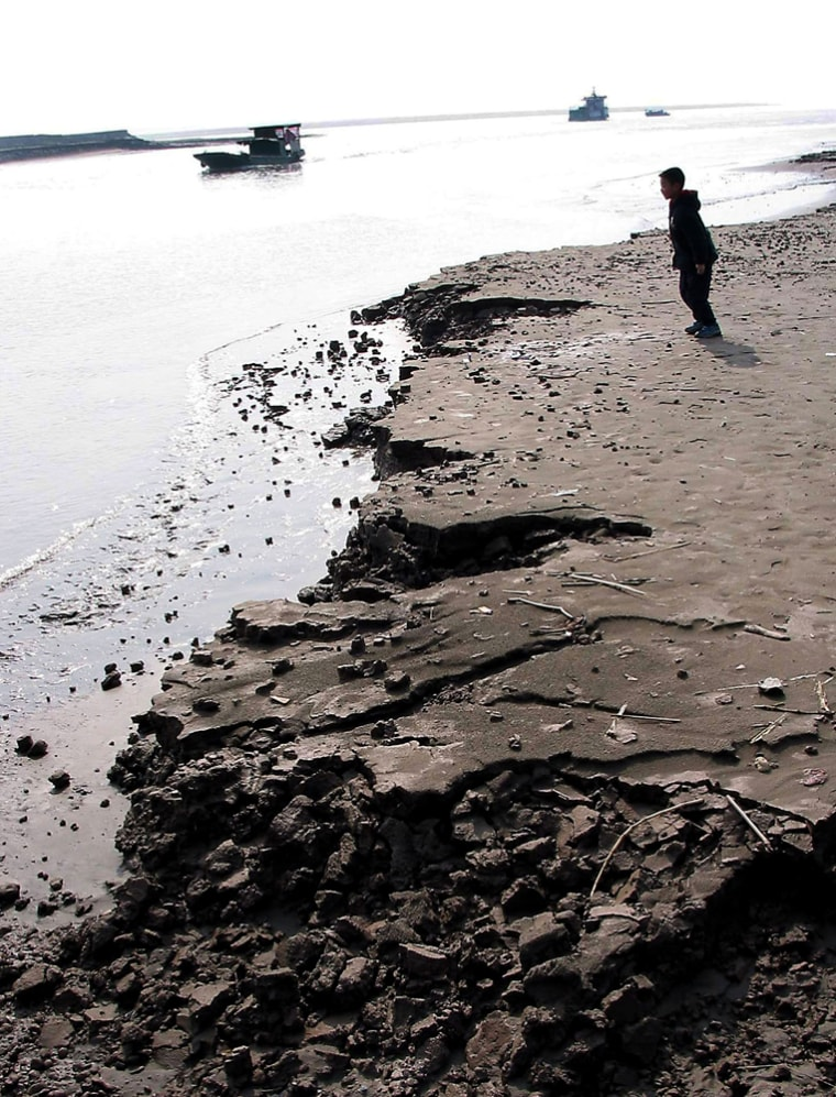 A Chinese boy plays by the eroding banks