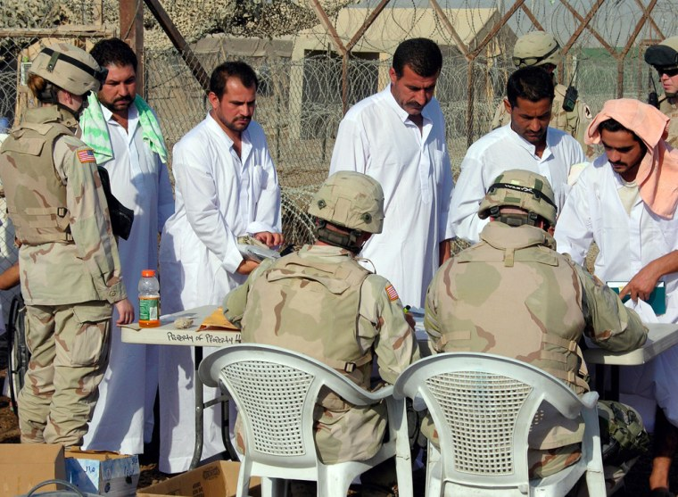 Former detainees wait their turns at sign-out table as US Army soldiers process them out of Abu Ghraib prison in Baghdad