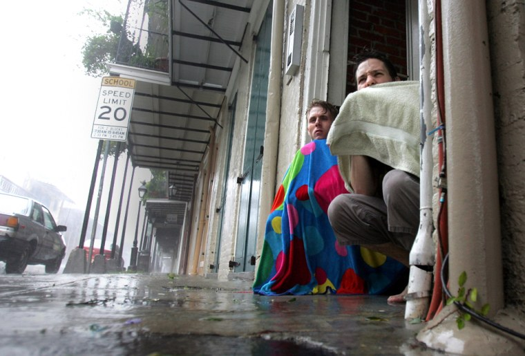 Blair Quintana, right, and Patrick Lampano seek shelter in a doorway in the French Quarter of New Orleans as Hurricane Katrina pounds the Crescent City on Monday.