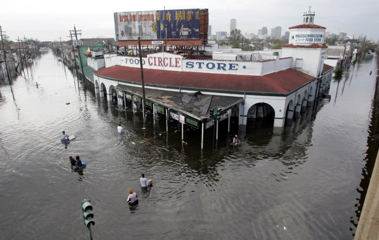 Looters make their way Tuesday into and out of a grocery store in New Orleans, where floodwaters continue to rise.