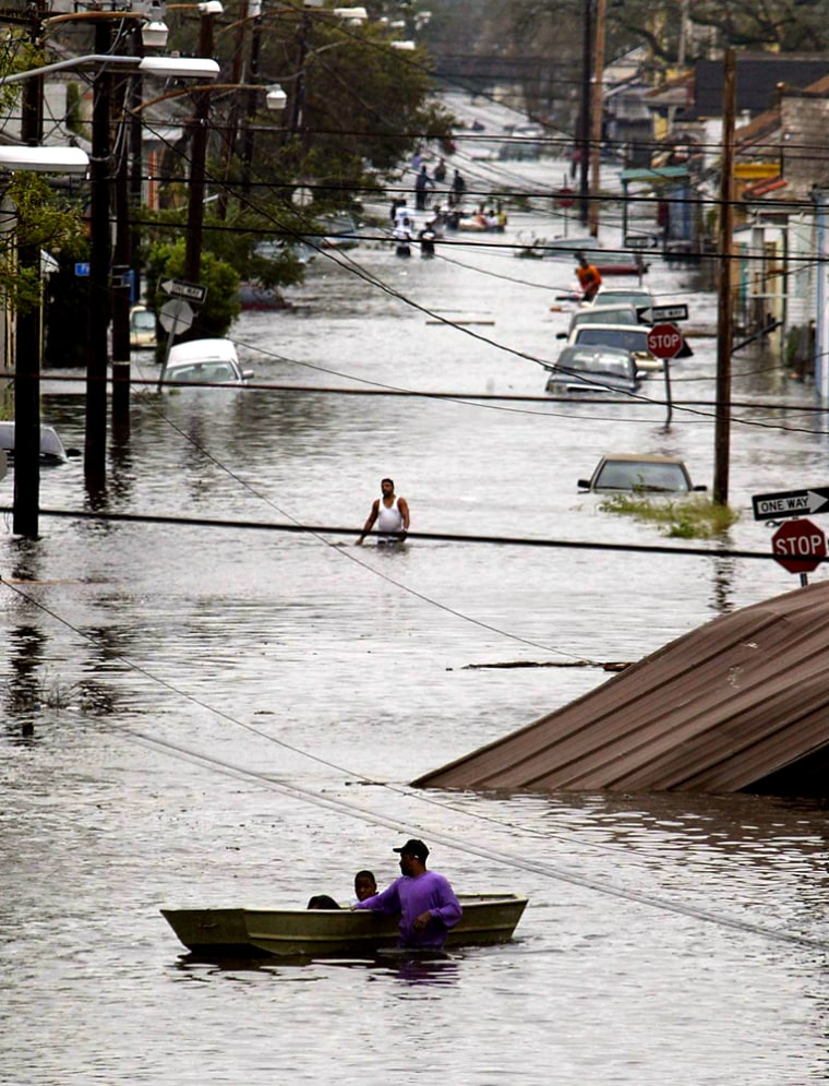 Residents wade through a flooded street