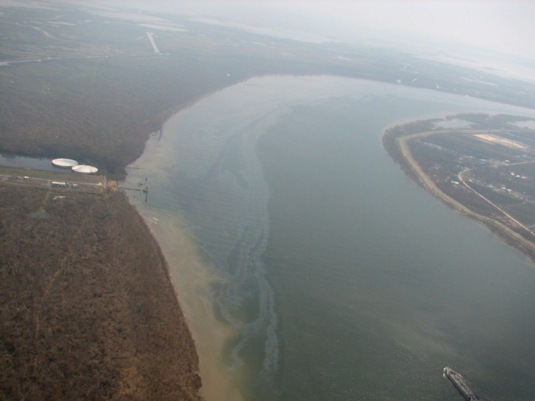 """The sheen from an """"oil-like slick"""" on the Mississippi River is seen Thursday. At left are two storage tanks that officials fear might be leaking oil."""