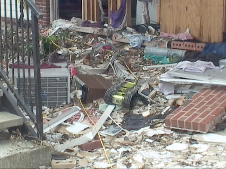 A yellow-green robot with black tracks, equipped with a video camera,climbsdown a pile of rubble after inspecting a ruined apartment building in Biloxi, Miss. The robot inspection confirmed there were no survivors inside the unsafe structure.