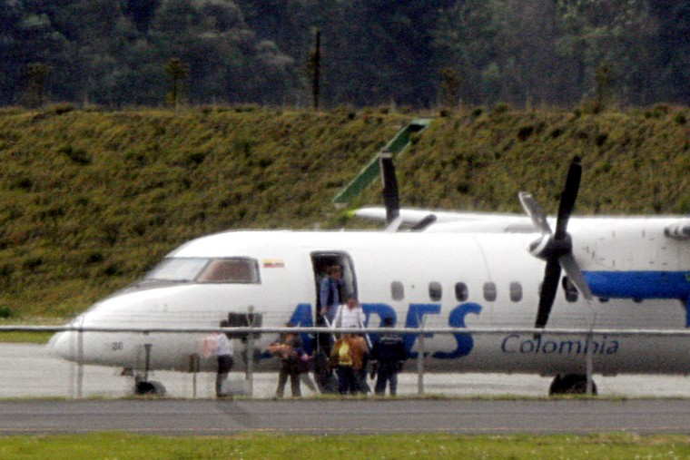 Passengers of a hijacked Colombian airliner leave the planeafter it landed inBogota on Monday.