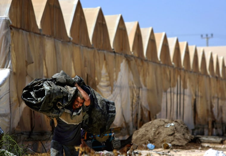 A Palestinian carries a plastic roll he took Tuesdayfrom a greenhouse, background, at the evacuated Jewish settlement of Neve Dekalim in the Gaza Strip.