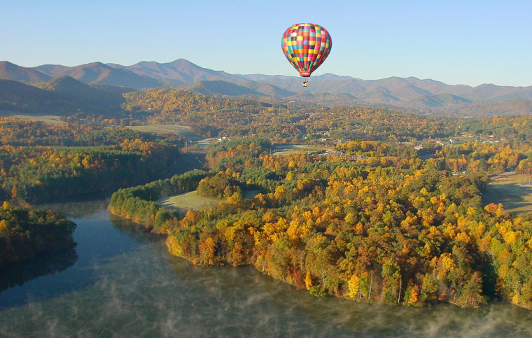 In this photo provided by the Asheville Convention and Visitors Bureau,ahot air balloon soars over Enka Lake in South Asheville, N.C., with Mount Pisgah and the Blue Ridge Mountains in the background.