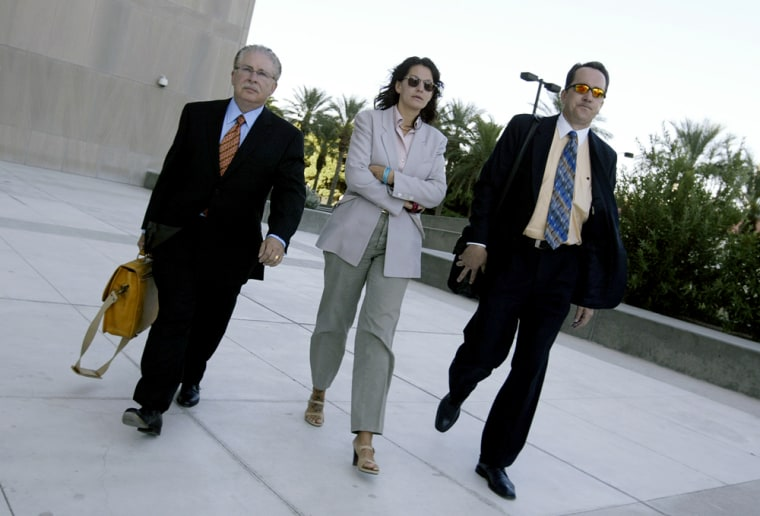 Heather Catherine Tallchief, flanked by attorneys, turns herself in to authorities in Las Vegas on Thursday, 12 years after she allegedly drove off in an armored car containing $3.1 million.