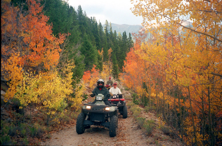 Connie Bauer, front, Mike Dean, center, and Roy Yablonka, rear, participate in the Buena Vista, Colo., ATV Historical Color Tour while riding through an Aspen canopy in the old mining district of Twin Lakes Village Sept. 3, 2003.