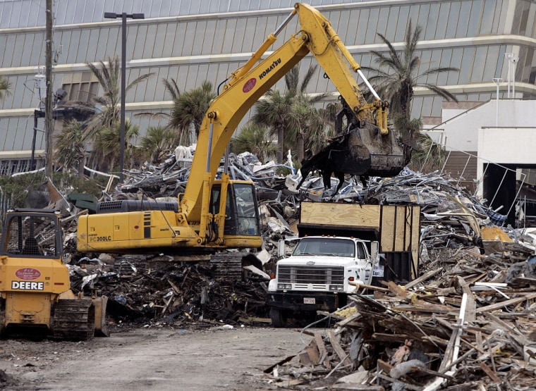 Trucks are loaded with debris from Hurricane Katrina in Biloxi, Miss., Friday.