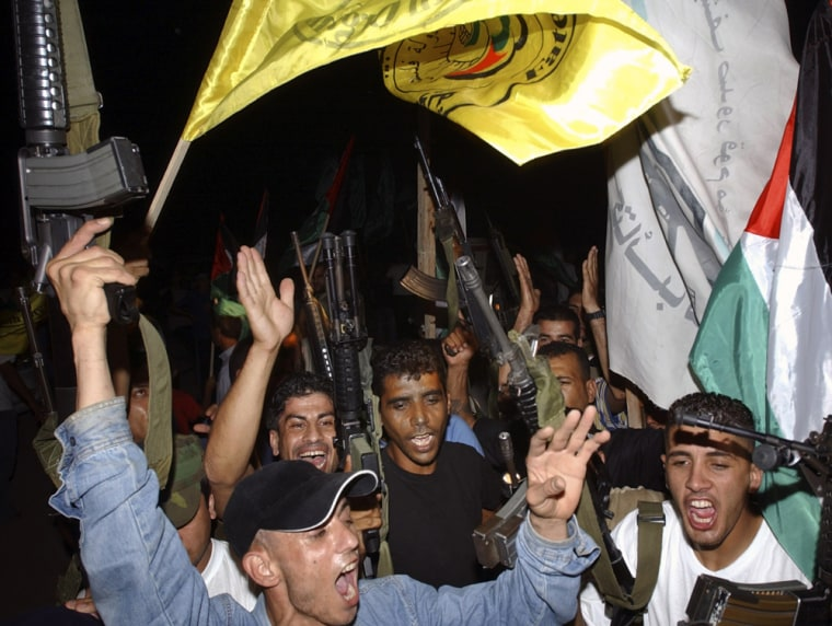 Members of the Palestinian militant group Al Aqsa Martyrs Brigades celebrate after the Israeli army left the northern West Bank Jewish settlement of Qadim on Tuesday.