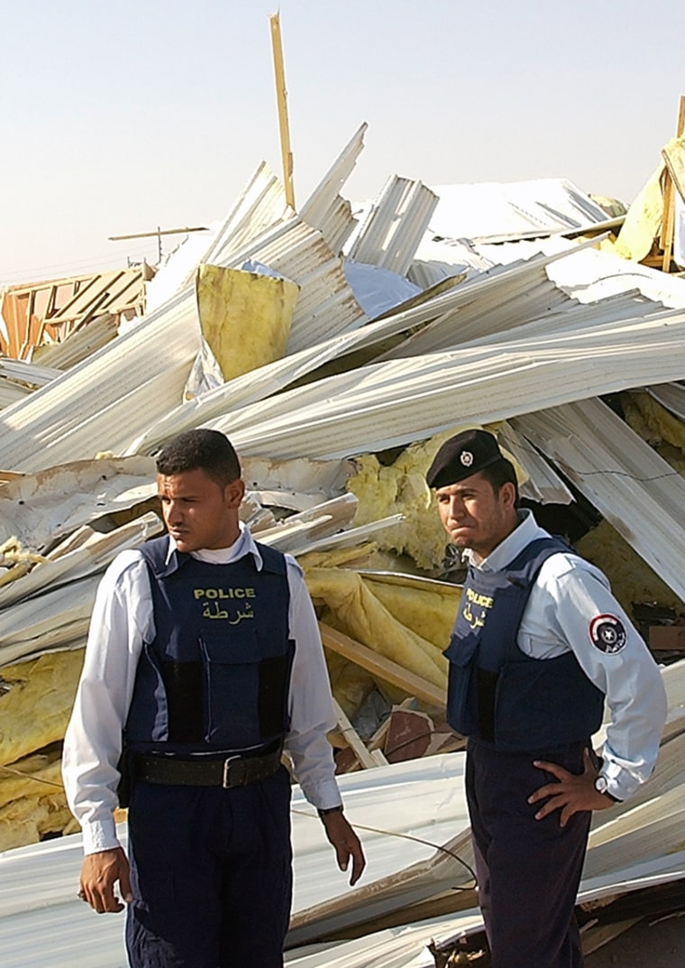 Iraqi police officers stand near debris at the central jail in Basra, Iraq, on Tuesday. British armored vehicles broke down the walls of the jail to free two British soldiers, arrested for shooting two Iraqi policemen. The men were later found to be held by militants in another location.
