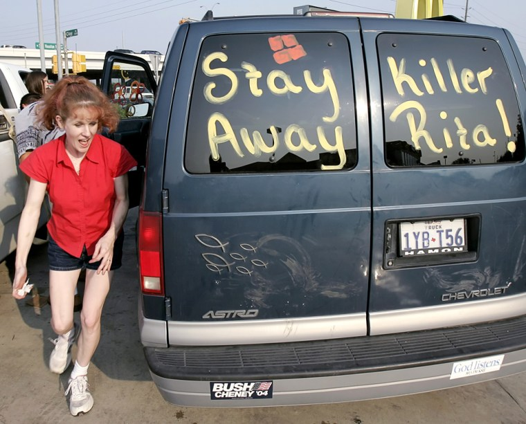 Leighan Cortez runs to get in her van that is painted with references to Hurricane Rita in east Houston
